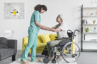 cuidador-que-ayuda-al-paciente-femenino-mayor-que-sienta-silla-rueda_23-2147861519